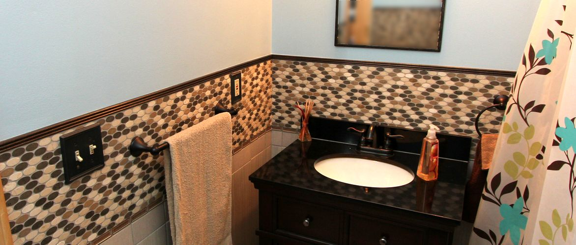 Fancy tile wainscotting and a furniture style vanity are featured in this bathroom makeover.