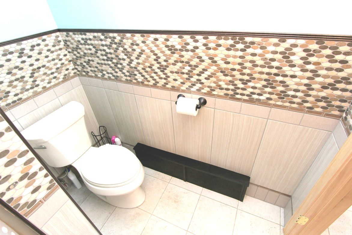 New toilet and fancy tile wainscotting.