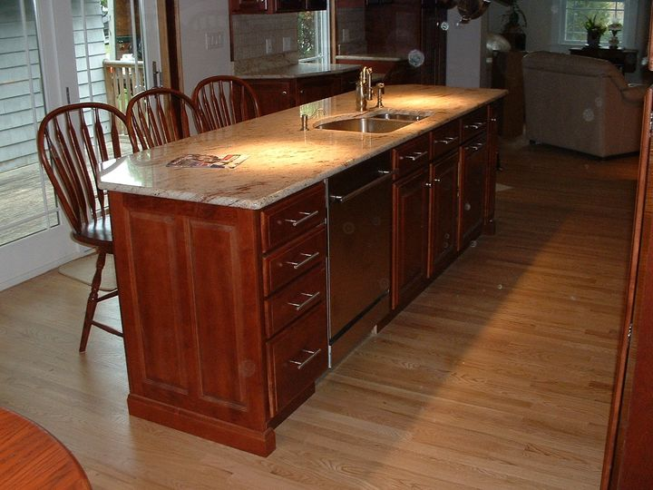 kitchen island with a granite top, and stainless sink and dishwasher