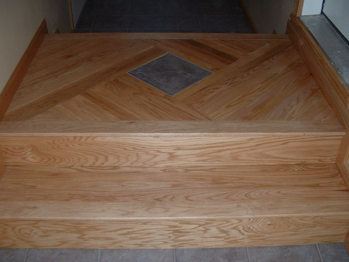 Oak entry steps, with a single tile inlaid on the landing.