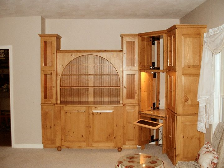 knotty pine cabinets with some doors open revealing a computer work area