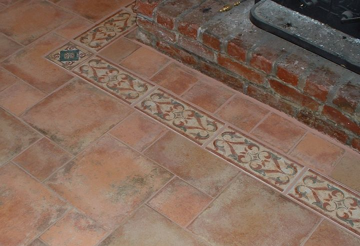 Decorative tile border surrounds the hearth in this tile floor.