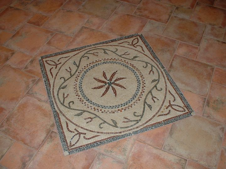 Intricate marble mosaic inlain in a ceramic tile floor.